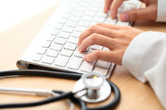 Doctor typing in keyboard with stethoscope Stock Photo