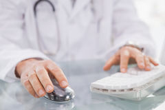 Doctor typing on keyboard and using mouse Royalty Free Stock Photos