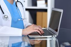 Doctor typing on laptop computer while sitting at the glass desk in hospital office. Physician at work. Medicine and. Healthcare concept Stock Photography