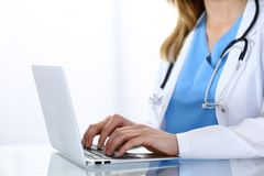 Doctor typing on laptop computer while sitting at the glass desk in hospital office. Physician at work. Medicine and. Healthcare concept Royalty Free Stock Photos