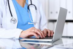 Doctor typing on laptop computer while sitting at the glass desk in hospital office. Physician at work. Medicine and stock photo