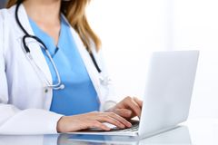 Doctor typing on laptop computer while sitting at the glass desk in hospital office. Physician at work. Medicine and stock image
