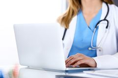 Doctor typing on laptop computer while sitting at the glass desk in hospital office. Physician at work. Medicine and royalty free stock photography