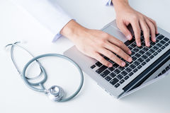 Doctor typing on a laptop. Doctor at work, close up of male doctor typing on a laptop Royalty Free Stock Photos
