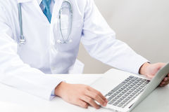 Doctor typing on a laptop. Doctor at work, close up of male doctor typing on a laptop stock images