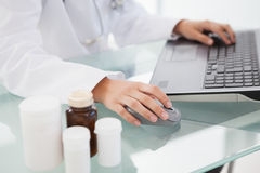 Doctor typing out prescriptions. In her office Royalty Free Stock Photography