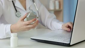 Doctor typing report on laptop keyboard, checking information on pharmacy bottle. Stock footage stock video