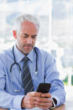 Doctor typing a text message on his smartphone. Attractive doctor typing a text message on his smartphone Stock Photo