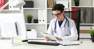 Doctor typing text on white tablet in office.  stock video