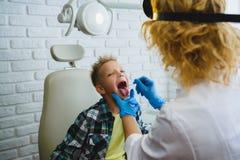Doctor u otorrinolaringólogo Ent que examina una garganta del niño Fotos de archivo libres de regalías