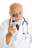 Doctor - Under Scrutiny. Handsome mature doctor examines you with his otoscope.  Isolated on white Royalty Free Stock Images