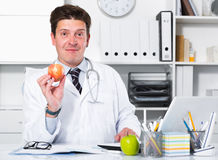Doctor in uniform demonstrating benefit of apples. Young and smiling doctor in uniform demonstrating benefit of apples Stock Photos
