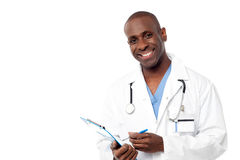 Doctor in a uniform holding a clipboard. Smiling male physician writing prescription Royalty Free Stock Photography
