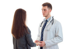 Doctor in uniform holds his patient`s hand and looking at her Stock Photos