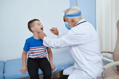 Doctor in uniform in mask treating young patient. Portrait of doctor in uniform and mask working with little patient in hospital. Professional doctor helping royalty free stock image
