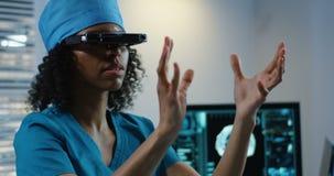 Doctor usando las auriculares de VR durante la discusión de diagnosis almacen de video