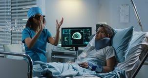 Doctor usando las auriculares de VR durante la discusión de diagnosis almacen de metraje de vídeo