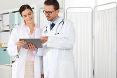 Doctor use the tablet, with intern, concept of medical consult Royalty Free Stock Photography