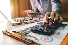 Doctor used a calculator and tablet for medical costs. Healthcare costs and fees concept.Hand of smart doctor used a calculator and tablet for medical costs at royalty free stock photos