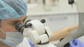 Doctor used microscope. Dentist is treating patient in modern dental office. Orthodontist work with assistant. Operation. Doctor used microscope. Dentist is stock video footage