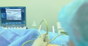 A doctor uses a modern sonogram to view vein in sclerotherapy procedure. An innovative method of varicose veins surgery. Close-up stock footage