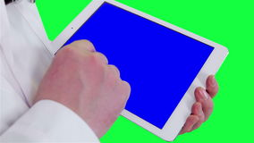 Doctor uses a tablet computer closeup. Chroma key background stock footage
