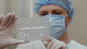 Doctor uses tablet with text Downloading. Doctor in mask interacts futuristic hud screen tablet with text Downloading. Medical concept of future technology stock video footage