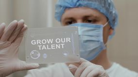 Doctor uses tablet with text Grow our talent. Doctor in mask interacts futuristic hud screen tablet with text Grow our talent. Medical concept of future stock footage