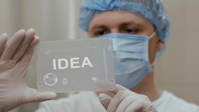 Doctor uses tablet with text Idea. Doctor in mask interacts futuristic hud screen tablet with text Idea. Medical concept of future technology. Futuristic doctor stock video footage
