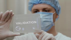 Doctor uses tablet with text Validation. Doctor in mask interacts futuristic hud screen tablet with text Validation. Medical concept of future technology stock video footage