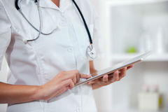 Doctor using app on a tablet computer Royalty Free Stock Photography