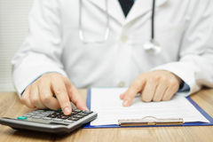 Doctor is using calculator to sum all of expenses Royalty Free Stock Image