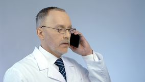 Doctor using cellphone to arrange meeting, remotely monitoring treatment process stock image