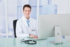 Doctor using computer at desk in clinic Stock Photos