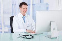 Doctor Using Computer At Desk In Clinic Stock Image