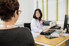 Doctor Using Computer While Looking At Patient At Desk Stock Photography