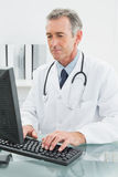 Doctor using computer at medical office Stock Photo