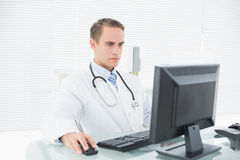 Doctor using computer at medical office Stock Images
