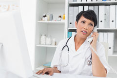 Doctor using computer and telephone Stock Photography