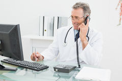 Doctor using computer and telephone at office Royalty Free Stock Image