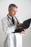 Doctor using computer vertical. Doctor typing notes or information into a computer Royalty Free Stock Images