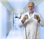 Doctor using a defibrillator Royalty Free Stock Images