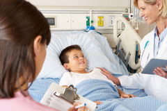 Doctor Using Digital Notepad Whilst Visiting Child Patient Stock Images