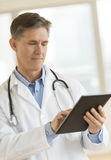 Doctor Using Digital Tablet In Clinic. Mature male doctor using digital tablet while standing in clinic Royalty Free Stock Photos