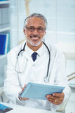 Doctor using digital tablet at clinic Stock Photos