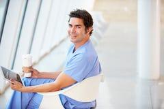 Doctor Using Digital Tablet On Coffee Break In Hospital Stock Photos