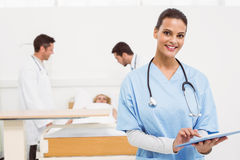 Doctor using digital tablet with colleagues and patient behind Stock Photography