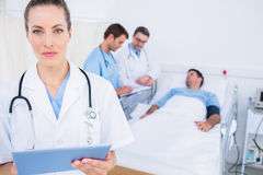 Doctor using digital tablet with colleagues and patient behind Stock Image