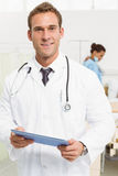 Doctor using digital tablet with colleagues and patient behind Royalty Free Stock Image