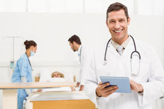 Doctor using digital tablet with colleagues and patient behind Stock Images